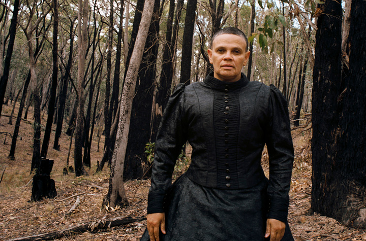woman wearing black standing in forest setting