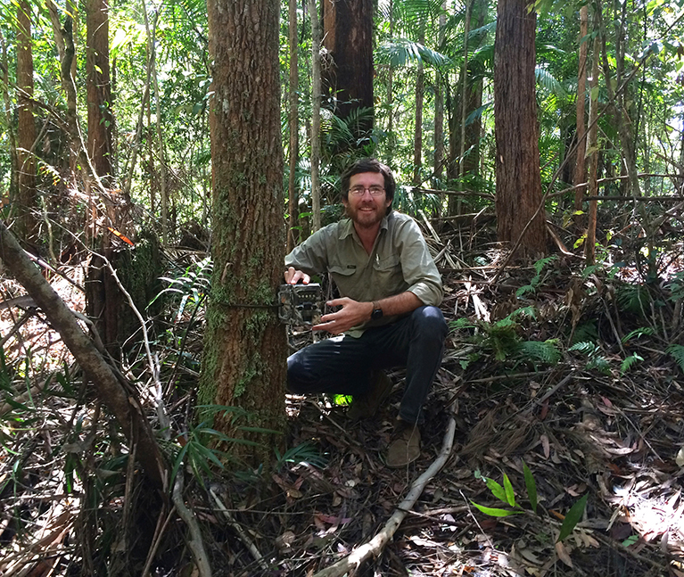 Darren McHugh sets up a camera trap in unburnt forest of Nightcap National Park