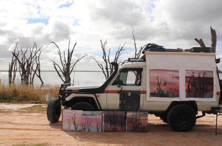 Four wheel drive vehicle with several artworks leaning on it parked beside a lake