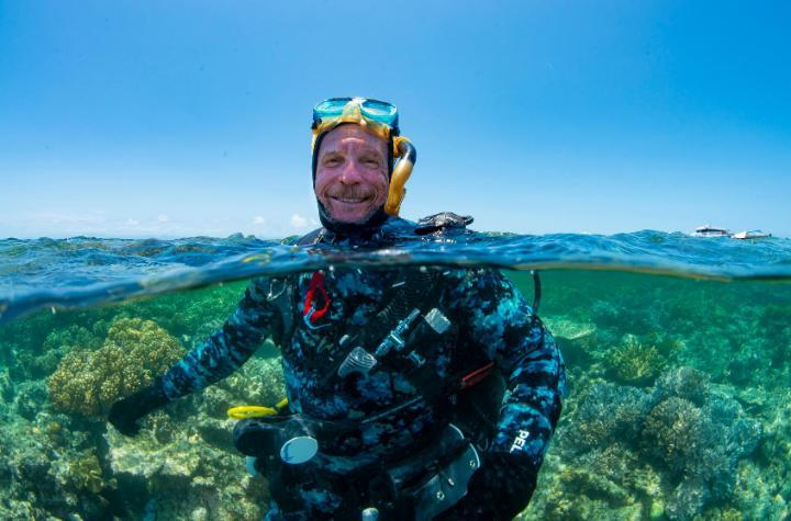 Scuba diver emerging from the ocean surrounded by coral reef