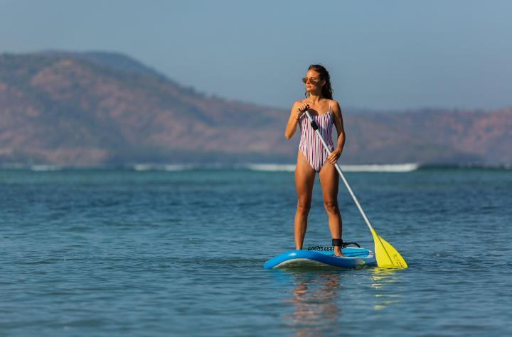 Woman on a blue stand-up paddleboard holding a yellow oar