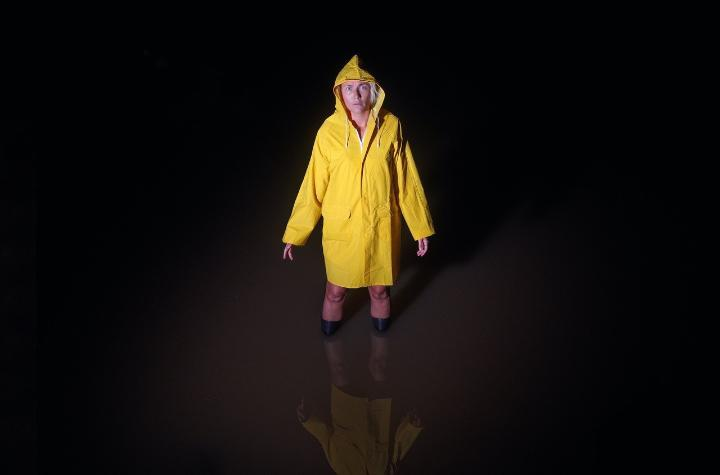 Woman in a yellow raincoast and wellington boots standing in kneehigh water