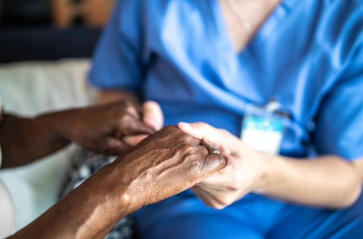 Healthcare working holding person's hand
