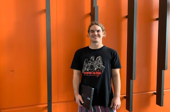 A man in a black tshirt holding a laptop in front of an orange-coloured wall